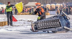 Out Of The Race (Wes Iversen) Tags: michigan nikkor18300mm stcharles bales bottom crowds helmets ice people snow snowmobileracing snowmobiles underside wreck yellow yellowflag
