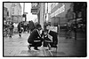 THE CROUCHING SMOKER. (StockCarPete) Tags: bw london londonstreets smoker reflection kneeling hat earphones pavement shops wetpavement londoners male man crouching