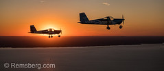 Two Vans RV-12 light sport aircrafts fly in formation together with the dramatic setting sun behind them on the Chesapeake Bay, Stevensville, Maryland. (Remsberg Photos) Tags: aircraft airplane aviation flying lightsport lsa pilot plane rv12 sport tandem vansaircraftrv12 alsa twoseat singleengine lowwing homebuilt americanaircraft vehicle transportation soar travel journey stunt propeller sky outdoors excitement privateairplane sunset sunshine dramatic adventure risk skill chesapeakebay exhilarating aerial intheair winged flight motion sunlight warmth settingsun sundown stevensville maryland usa
