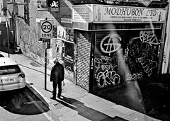 Buckfast St (I M Roberts) Tags: buckfastst bethnalgreen bethnalgreenrd london e2 no26bus urbansetting graffiti tagging manwalking bw fujix100s