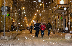 Beautiful But Cold (kaprysnamorela) Tags: city street snow winter outdoor flakes people buildings lamps lights
