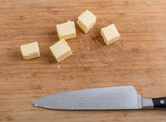 Chopped butter. (annick vanderschelden) Tags: butter churningbutter dairy butterfat solid chilled roomtemperature churning paper packaging white fermented cream grey proteins buttermilk refrigerated yellow pale unhomogenized milk microscopic phospholipids agitatingcream knife