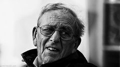 In a world that often takes itself too seriously. (Neil. Moralee) Tags: neilmoralee neilmoraleesidmouth man face portrait street candid glasses wind windswept blowing hair balding old mature senior smile teeth uneven black bw white bandw blackandwhite whiteandblack close mono monochrome neil moralee nikon d7200 solo looking lookingovershoulder lookback devon sidmouth uk sundaylights