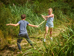 Beating about the Bush 15 (C & R Driver-Burgess) Tags: girl boy preteen young woman niece son curly blonde hair reeds rushes toitoi sticks play fight fencing dual battle pretend fun share shortalls denim track pants lacy singlet black tshirt dry summer sun forest clearing path bush native new zealand aotearoa two together pair cousins