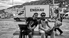 Enghav (Anne Worner) Tags: anneworner blackandwhite ricohgr architecture bw bench buildings candid cap cobblestones computer headset mast men monochrome sidewalk sitting smiling street streetphotography sunglasses tourists truck walking woman mp34player pc carrying shoppingbags glasses outside market bergen norway harbour