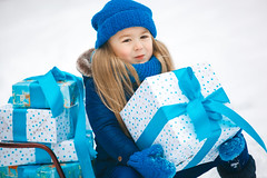 Little girl holding a christmas gift in her hands and emothionally smiling. Child wearing a blue knitted hat, gloves, mittens, scarf (elenachukhil) Tags: winter daughter smiling hat knitted white blue caucasian little girl snow laughing family care celebration happy birthday christmas new year love child present joy spruce scarf mittens gloves cold frost fun emothional snowflake face portrait xmas newyear childhood pretty cute happiness casual cheerful holiday joyfulsled sleigh many outdoors outside background copyspace copy space