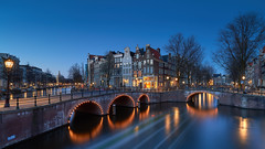 Blauw Amsterdam (zsnajorrah) Tags: urban urbanphotography city cityphotography bridge water canal reflection lights nightlights streetlight canalhouses storefronts downtown citycentre trees lighttrails boat transportation evening sky bluehour night nightphotography longexposure neutraldensityfilter nd breakthroughphotography x4nd2 tiffen gradnd manfrotto redged canon 7dmarkii efs1018mm netherlands amsterdam keizersgracht leidsegracht grachtengordel twilight dusk motion