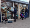 Window Shopping (M C Smith) Tags: shop people men windows shopping looking street pavement pushchairs painting blue pink reflections sky trees houses letters symbols numbers bag rucksack