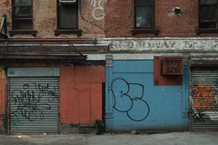 Painted Building Fronts (Zach K) Tags: newyork unitedstates usa brooklyn nyc painted blue red storefront building facade graffiti pretty but urban gritty olympus epl2 roll down gate