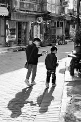 (perryge) Tags: streetphotography candid people boys gun brothers shadow film blackandwhite bw walking saikung hongkong newterritories urban city street shadows