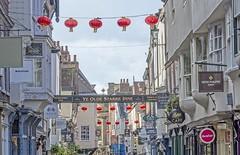York: Stonegate celebrates the Chinese new year. (jack cousin) Tags: york yorkshire stonegate street shops shop shopsigns buildings sky cloud shopfont brickbrickwork roof tiles slate chimney window shopping