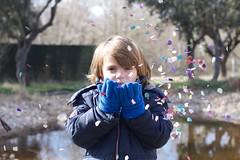 blowing confetti (AriCatalán) Tags: jackierueda frozenmovement movimientocongelado bokeh child confetti retrato portrait confeti kid niño boy blowing lake