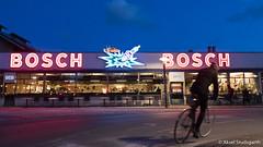 Bosch Neon with Cyclist (mistermacrophotos) Tags: copenhagen by night denmark city urban winter neon kødbyen bio mio bosch bob meat packing district vesterbro spark plug blue red colorful