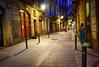 Gothic Quarter street in Barcelona, Spain (` Toshio ') Tags: toshio barcelona spain spanish gothicquarter barrigòtic barriogótico woman street night historic city road architecture europe european euorpeanunion fujixe2 xe2 people door dress walking travel