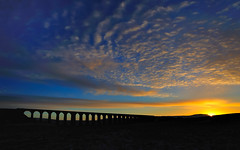 Dawn ignition (images@twiston) Tags: justbreaking ribblehead viaduct ribbleheadviaduct settle carlisle settlecarlisle yorkshire northyorkshire midland railway main line 1875 battymoss battywifehole sebastopol belgravia jericho scheduledancientmonument 24 arch arches ribblesdale dales 3peaks yorkshire3peaks penyghent golden morning national park yorkshiredalesnationalpark moorland moor blue sky sunrise dawn clouds orange silhouette silhouettes silhouetted landscape imagestwiston my365year twentyfour fells manmade stonework shadow shadows sweeping curve curved wide angle godsowncountry