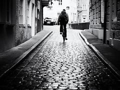 Biker (Sandy...J) Tags: olympus atmosphere alone city cobblestones blackwhite bw biker street streetphotography sw monochrom man germany deutschland rain reflection urban noir cyclist fotografie photography