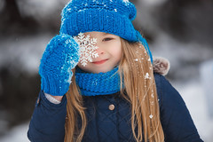 Little girl holding a snowflake in front of her face and smiling. Child wearing a blue knitted hat, scarf, gloves or mittens, looking at camera. Winter background (elenachukhil) Tags: winter daughter smiling hat knitted white blue caucasian little girl snow laughing family care celebration happy birthday christmas new year love child present joy spruce scarf mittens gloves cold frost fun emothional snowflake face portrait xmas newyear childhood pretty cute happiness casual cheerful holiday joyful