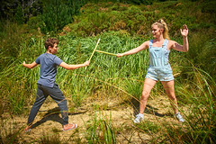 Beating about the Bush 05 (C & R Driver-Burgess) Tags: girl boy preteen young woman niece son curly blonde hair reeds rushes toitoi sticks play fight fencing dual battle pretend fun share shortalls denim track pants lacy singlet black tshirt dry summer sun forest clearing path bush native new zealand aotearoa two together pair cousins