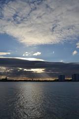 setting sun (curly_em) Tags: sunset portsmouth hampshire sky clouds pattern bluesky coastline coast water sea grey buildings sunshine sunrays