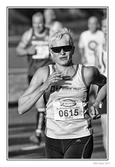 Showing The Way (Seven_Wishes) Tags: newcastleupontyne scotswoodroad canoneos5dmarkiv canonef100400mmf4556lisii photoborder jo outdoor blaydonrace blaydonrace2017 roadrace people streetphotography candid portrait athlete athletic sporting runner running femaleathlete dof depthoffield lycra bw mono monochrome blackandwhite runningvest fit woman sunglasses 2017