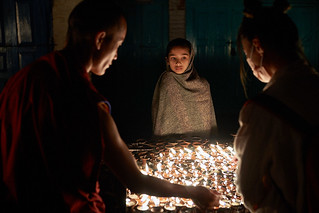Nepali girl lighting buddhist candles, Boudhanath, Kathmandu, Nepal 2