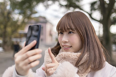 Young woman taking selfie picture in public park (Apricot Cafe) Tags: img80127 asia asianandindianethnicities healthylifestyle japan japaneseethnicity tamronsp35mmf18divcusdmodelf012 tokyojapan beginnings bonding candid carefree casualclothing charming closeup cold colorimage day domesticlife family finger happiness hopeconcept humanface lifestyles loveemotion mother newlife oneperson onlyjapanese outdoors people photographing photography pregnant publicpark realpeople relaxation selfie smartphone smiling straighthair sustainablelifestyle wife winter women youngadult