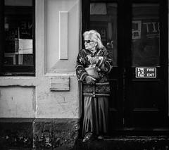 Waiting in the cold (raymorgan4) Tags: royal george hotel cardiff cold day fujifilm fujifilmx100f acros sunglasses grey hair lady long dress wales blackandwhite monochrome street urban scene candid unposed warm cardigan winter