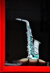 Sax appeal (Roving I) Tags: plastic saxophones music musicalinstruments windowdisplays goldcushions shops retail danang vertical vietnam