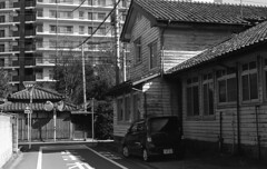 Old and new (odeleapple) Tags: nikon f2 nikkor 50mm yellowfilter kodaktmax100 film monochrome condominium gate house building road car