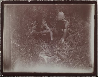 Two people sitting in the grass in front of a shot jackal. The one on the right is Jorma Gallen-Kallela.