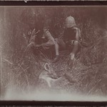 Two people sitting in the grass in front of a shot jackal. The one on the right is Jorma Gallen-Kallela. thumbnail