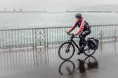 Wet Commuter (Rupert Brun) Tags: geneva lake cyclist commute commuter wet rain soak soaked raining pouring bicycle red water reflection