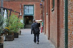 Dinner Delivery - Corktown, Toronto. (edk7) Tags: nikond300 edk7 2008 canada ontario toronto corktown distillerydistrict distilleryhistoricdistrict distilleryheritagedistrict distillerydistrictnationalhistoricsite victorian heritage industrial museum gooderhamwortslimited gooderhamworts 19thc whiskey 19thcvictorianwhiskeyfactorycomplex relic artefact wood architecture building oldstructure person male wall brick door pot plant pavement cobblestone
