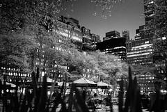 A lighter side of noir (Joann Edmonds) Tags: rollfilmweek kodakbw400cn 35mm olympusxa blackandwhite monochrome grainisgood nyc newyork bryantpark night citylights spring blossoms cityscape