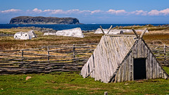 Norse building and old boats (Brett of Binnshire) Tags: historicbuilding building lanseauxmeadows ocean water mountains highdynamicrange meadow shoreline weather boat clouds mountain hdr historicrecreation field lrhdr museum canada locationrecorded scenic lightroomhdr architecture newfoundland historicalsite manipulations cliff fence