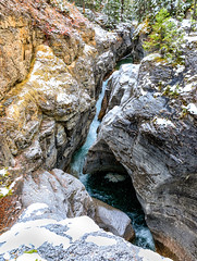 Maligne Canyon, Jasper National Park (aud.watson) Tags: canada alberta jasperregion jasper jaspernationalpark canadianrockies malignelakeroad malignecanyon maligneriver subalpineforest park reserve wildlifereserve nationalpark mountain mountains mountainside valley valleys canyon limestonecanyon gorge river riverbed riverpebbles riverrocks riverstones rock rocks ledge karsttopography waterfall rapids water pool pools erosion chockstones potholes snow ice mist snowing tree trees moss lichen rockencrustedlichen orangelichen xanthoriaelegans conifers pine pines spruce dryforestedmontane malignerange ca