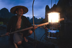 Legendary... (Syahrel Azha Hashim) Tags: singleexposure mountains tokina shallow simple dramaticsky guilin shadow 16mm touristattraction sunset conventional humaninterest handheld colorimage vacation destination china moment fishing d300s elder uwa mountain portrait lantern expression elite unique holiday chinese details portraiture xingping ultrawideangle bird local traditional dof bamboo smile fishermen nikon getaway bambooraft water clouds iconic birds scene light culture hat traditionalclothing colorful paddle cormorants travel syahrel naturallight river colors detail beard liriver oldman fisherman