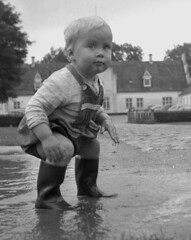 Ready to fall (theirhistory) Tags: children child boys kid toddler water puddle dungarees shorts wellies jumper wellingtons road flood