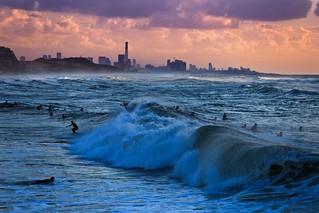 Surfing at sunset Tel-Aviv beach