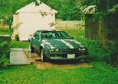 SANDYS 1982 CHEVY CAMARO IN JULY 1994 (richie 59) Tags: ulstercountyny ulstercounty newyorkstate newyork unitedstates trees generalmotors chevrolet townofesopusny townofesopus richie59 stremyny stremy america outside chevycamaro camaro summer automobile auto motorvehicle vehicle car oldphotograph olddays oldphoto film july1994 1994 photoscan 1982chevycamaro 1982camaro 1982chevy july251994 35mmfilm 35mm filmcamera filmphotography shed photograph photo hudsonvalley midhudsonvalley midhudson ny nys nystate usa us 1980scar americancar uscar 2door twodoor coupe chevycoupe chevy gm gmcar graycar faded fadedpaint frontend grill headlights grass woodenshed backyard yard oldcar oldchevy
