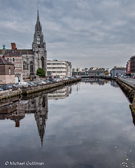 Further Reflections on the River Lee (Michael Guttman) Tags: cork ireland riverlee holytrinitychurch capuchinfriary church cathedral gothic spire reflections river city cityscape water buildings cars automobiles sky clouds cloudyskies reflection nikon d90