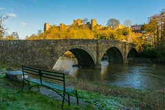 Dinham Bridge & Ludlow Castle (williamrandle) Tags: riverteme ludlow england shropeshire uk winter 2018 january dinhambridge bridge water stone arch structure castle ludlowcastle frost sunlight shade trees green bench landscape outdoors bluesky nikon d7100 sigma1835f18art tree grass sky building
