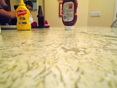 DSC03142 (classroomcamera) Tags: cook cooking eat eating kitchen house home ketchup catsup mustard frenchs heinz 57 granite counter countertop island smooth surface touch touching texture cold distance far away bottle stuff prep hot dogs ham burger dog burgers