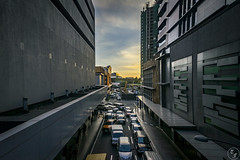 From an Overpass (Terra Firma Productions) Tags: photography photo landscape landscapes landscapephotography building buildings landscapephoto sunset sunsets road roads street streets car cars traffic person persons people cityscape cityscapes sony sonyalpha sonya7 sonya7ii adobe adobephotoshop adobelightroom photoshop lightroom intersection intersections crossing crossings