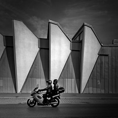 Triumph (heinzkren) Tags: blackandwhite bw monochrome panasonic lumix urban traffic verkehr building motorrad street streetphotography wien vienna austria stadthalle couple schwarzweis motorcycle motorbike architecture