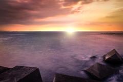 Journey into eternity III (Lluvia Fotografia) Tags: down sunset rocks sunshine beach longexposure orange reflection landscape seascape breakwater dream fantasy