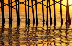 Under the Pier (Karen_Chappell) Tags: travel sunset orange ocean pacific usa orangecounty california beach balboabeach evening water sea ripples reflection reflections silhouette black pier