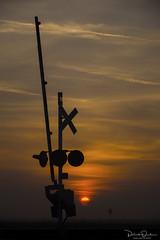 Sunrise on the Rails (Patrick Dirden) Tags: crossbuck crossingsignal railroadcrossing crossingstandard signal sign rail railroad bnsf bnsfrailroad bnsfrailway burlingtonnorthernsantafe burlingtonnorthernsantaferailroad bnsfstocktonsub sunrise dawn orange sun clouds silhouette sky legrand legrandca mercedcounty centralvalley sanjoaquinvalley northerncalifornia california