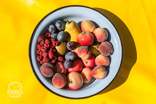 Bowl of freshly picked fruits on yellow background