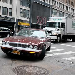 Jaguar (Zach K) Tags: maroon jaguar automotive auto red turning 8th avenue nyc midtown westmidtown car automobile english engineering crosswalk manhole driving navigating city fujifilm fuji luxury